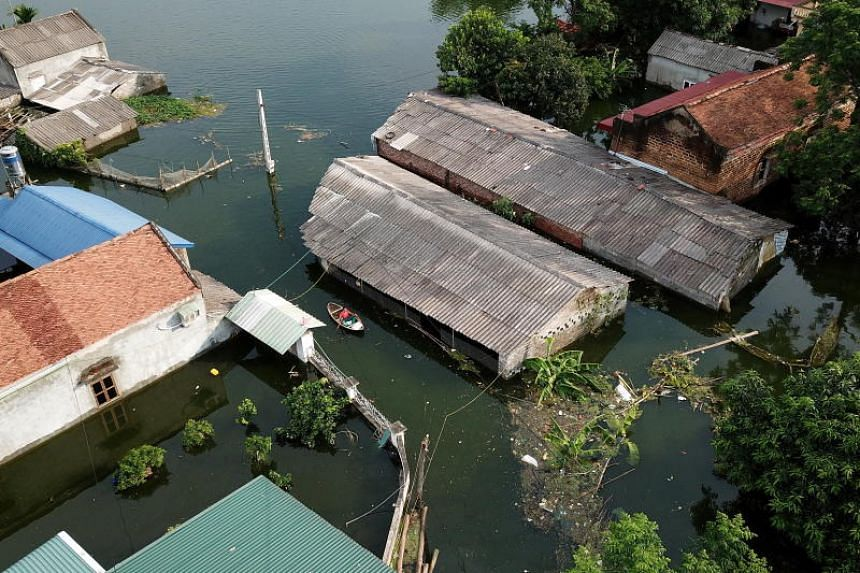 Flood waters surround houses in Nam Phuong Tien commune in Hanoi on July 30, 2018.