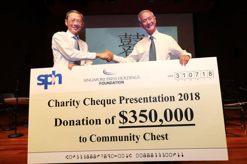 Dr Lee Boon Yang (left), chairman of Singapore Press Holdings (SPH) and its charity arm SPH Foundation, presenting a cheque to Mr Eric Ang, vice-chairman of Community Chest, at the Singapore Conference Hall on July 31, 2018.