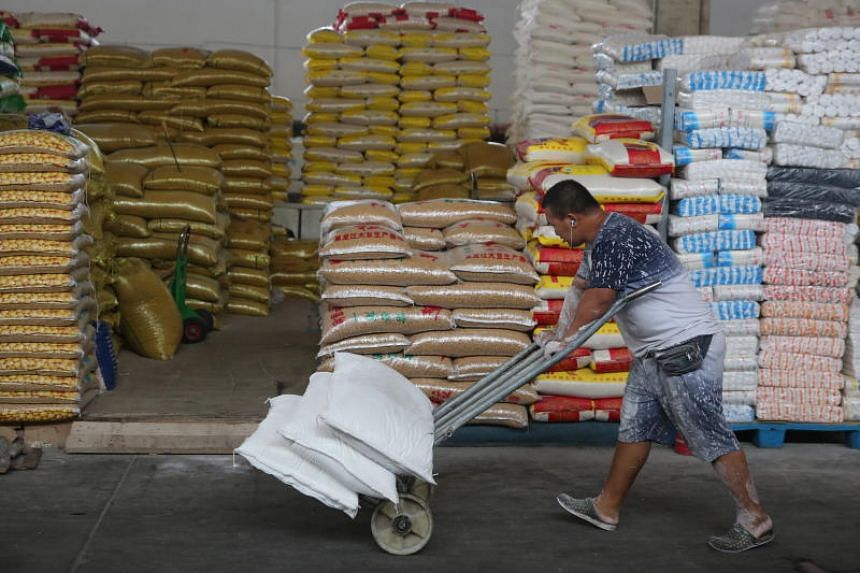 A Chinese man pushes a trolley past bags of soybean in a grain wholesale market in Beijing, China, on July 31, 2018.