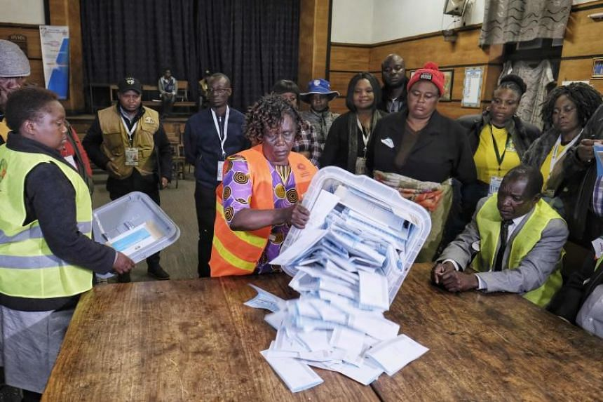 Electoral workers empty a presidential candidates ballot box onto a table during counting operations for Zimbabwe's general election at the David Livingston Primary school in central Harare on July 30, 2018.