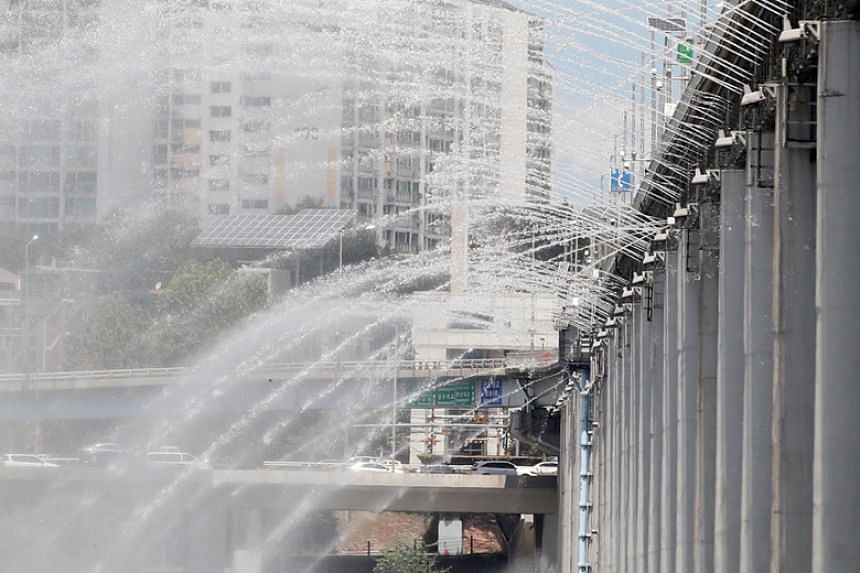 Water is sprayed amid sweltering heat at the Banpo Bridge over the Han River in Seoul on July 30, 2018.