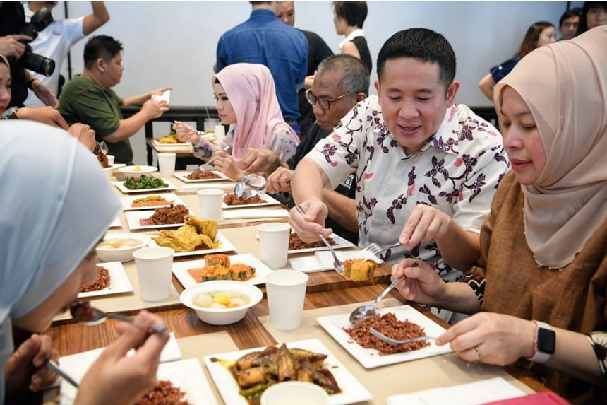 Mr Amrin Amin, Senior Parliamentary Secretary for Health, tasting some of Rumah Makan Minang's five new dishes, which have been endorsed as healthier options under the Healthier Dining Programme.