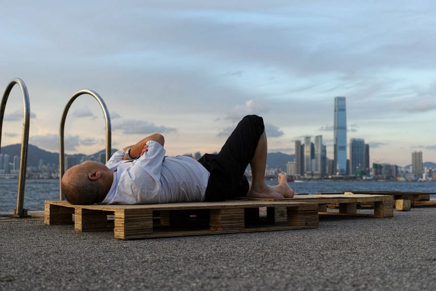 A man rests on a palette at sunset on a pier in Hong Kong, China.