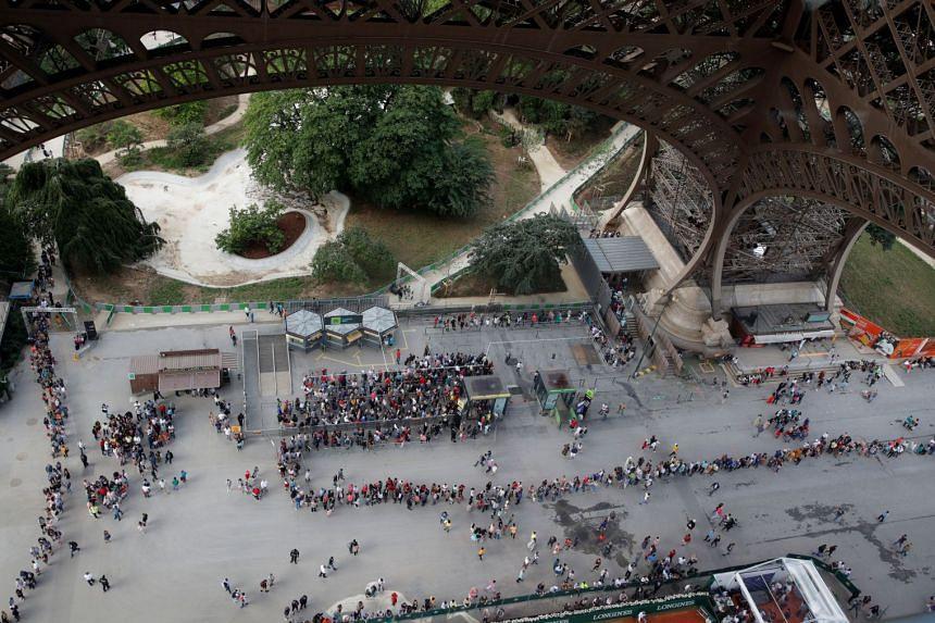 Visitors queue to visit the Eiffel tower in Paris on June 2, 2018.
