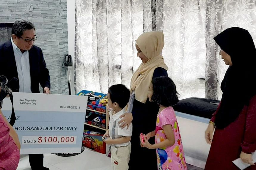 Komoco Motors finance director Philip Beng handing Nur Alam Shah's widow Azean Aziz a cheque for $100,000. Also pictured are her youngest son Muhammad Royyan, daughter Auni Syahindah, and mother Noraini Abdul Rahim.