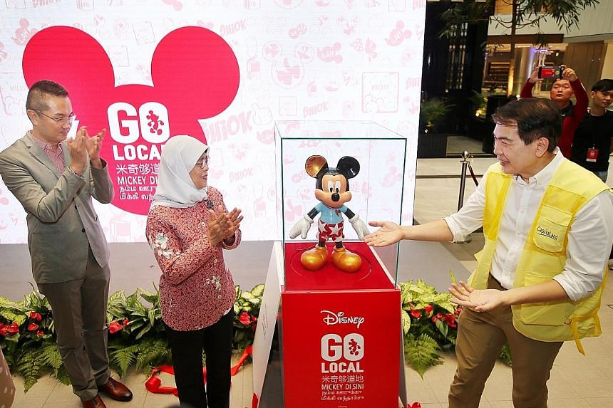 President Halimah Yacob, The Walt Disney Company Singapore executive director of marketing Daniel Tan (left) and CapitaLand president and group CEO Lim Ming Yan unveiling the President's Mickey Mouse figurine. Below: Actor Li Nanxing and actress-host