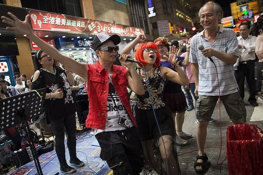 Buskers performing in Sai Yeung Choi Street South in Mong Kok, Hong Kong, last Saturday. In the wake of noise complaints, the local authorities will abolish the pedestrian zone, where the street performers have been entertaining crowds, and reopen it