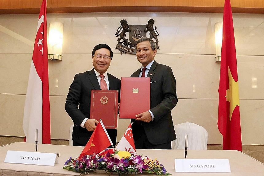 Vietnam's Deputy Prime Minister and Foreign Minister Pham Binh Minh (left) and Foreign Minister Vivian Balakrishnan after signing the agreement on the Vietnam-Singapore Cooperation Centre yesterday.