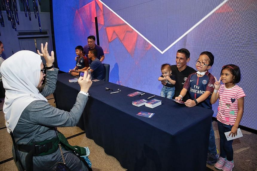 Juliana Mohamad taking a photograph of her children (from left) Muhd Firdaus Masli, Muhd Ridhwan and Nurin Insyirah with Paris Saint-Germain star Angel di Maria. His PSG team-mate Thiago Silva can also be seen at the meet-and-greet session held yeste