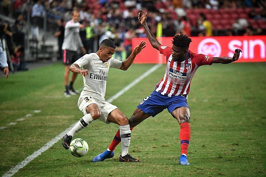 Atletico Madrid's Thomas Partey (right) challenges Paris Saint-Germain's Colin Dagba during the ICC match on Monday. When an agent took him from Ghana to Spain, his family did not know where he was.