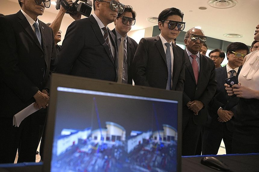 National Development Minister Lawrence Wong (fourth from left) wearing 3D glasses to look at a screen with a building scanned using a digitisation technique, after the launch of the SJ-NTU Corporate Lab yesterday.