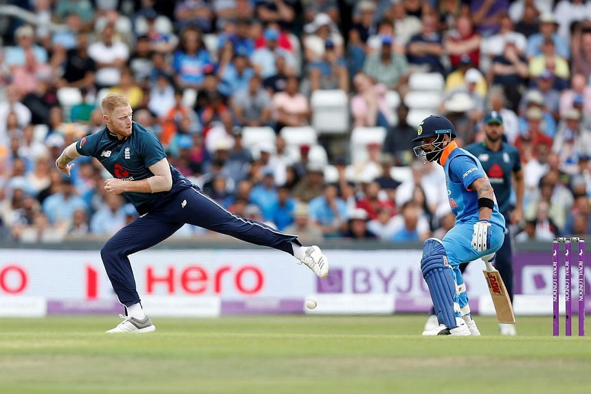 England's Ben Stokes attempts to stop the ball with his foot as India's Virat Kohli looks on.