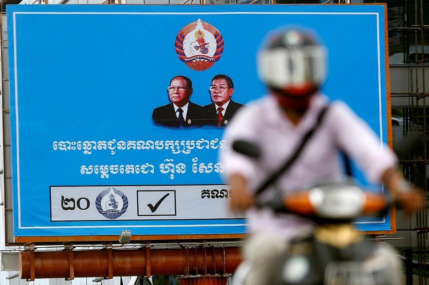 A man rides a motorcycle as a poster of the Cambodian People's Party is seen at Koh Pich island in Phnom Penh, Cambodia, on July 31, 2018.