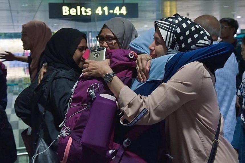 Madam Aishah Kamari hugging her daughter, Ms Insyirah Nur Azmi, at the airport.