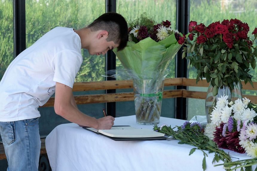 A man signs a book of condolences at the US Embassy in Dushanbe, on July 31, 2018, in tribute to the victims of the deadly attack.