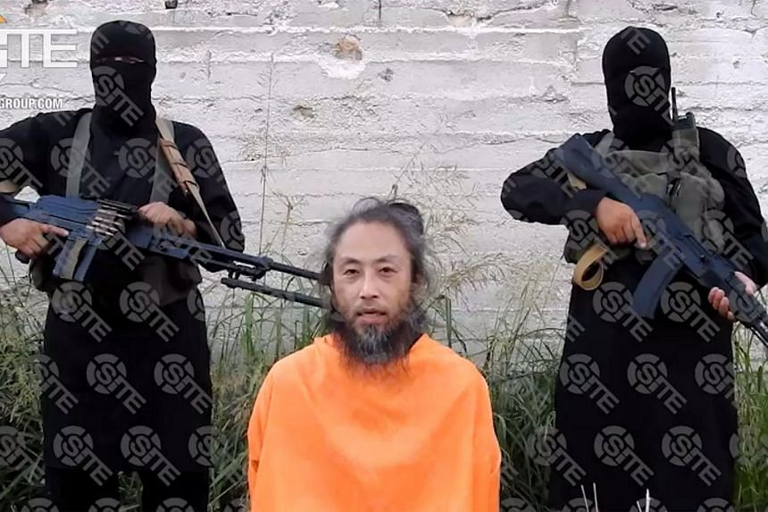 Japanese national, Yasuda Jumpei, appealing for his release as two armed men stand behind him at an unknown location in Syria. The photo is believed to be taken on July 25, 2018.