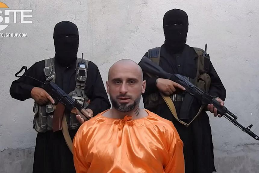 Italian national, Alessandro Sandrini, appealing for his release as two armed men stand behind him at an unknown location in Syria. The photo is believed to be taken on July 19, 2018.