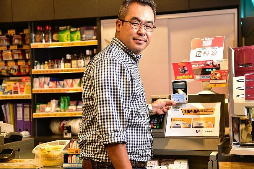 EZ-Link chief executive Nicholas Lee demonstrating how customers at Cheers convenience stores can use the change from their purchases to top up their ez-link cards. EZ-Link also aims to get users to migrate the monetary value stored on physical cards