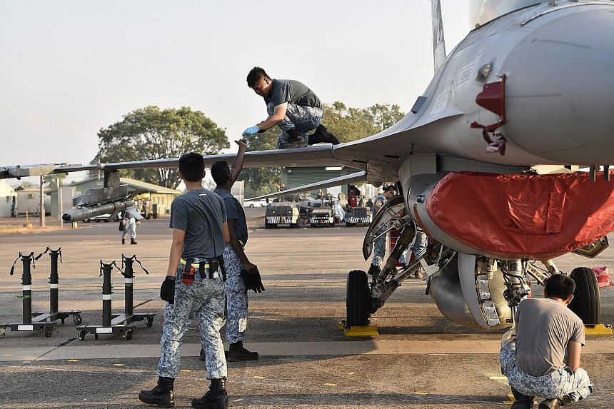 Above: The Republic of Singapore Air Force's (RSAF) KC-135 refuelling a Royal Australian Air Force plane. Right: RSAF engineers preparing an F-16C/D fighter aircraft for operations.