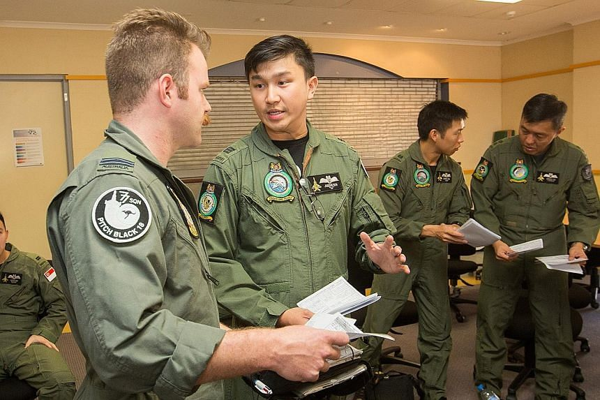 Captain Janzen Koh, a mission leader, discussing strategy with another leader from the Royal Australian Air Force's flight team. About 330 personnel from the RSAF are taking part in the largest operation of Exercise Pitch Black.
