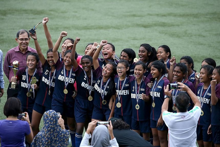 Bowen Secondary celebrating their 1-0 victory over rivals Queensway Secondary in the Schools National C Division girls' football final at the Singapore University of Technology and Design stadium yesterday. Nurhidayu Naszri scored the winning goal as