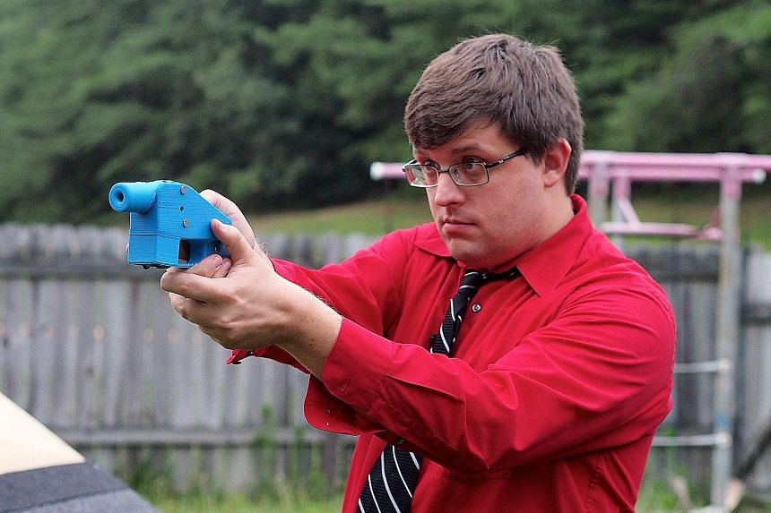 Photos taken in 2013 of software engineer Travis Lerol with a Liberator gun, and the 3D printer (above) which made its components.