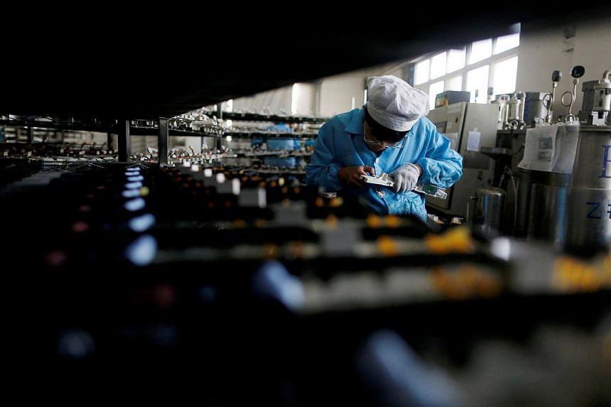 A labourer works inside an electronics factory in Qingdao, Shandong province, China, on Jan 29, 2018.