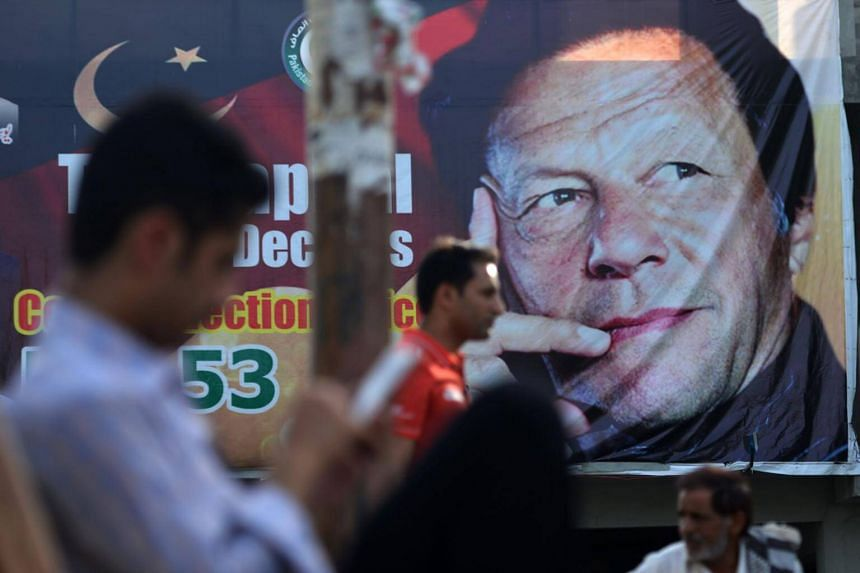 Pakistani men sit near a poster of Pakistan's cricketer-turned politician and head of the Pakistan Tehreek-e-Insaf party Imran Khan, in Islamabad, on July 30, 2018.