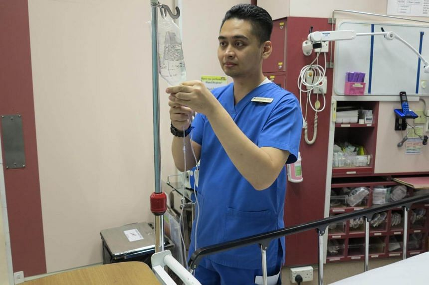 Mr Muhammad Shahabudin, a nurse manager at National University Hospital, preparing an intravenous drip for a patient at the hospital's emergency medicine department.
