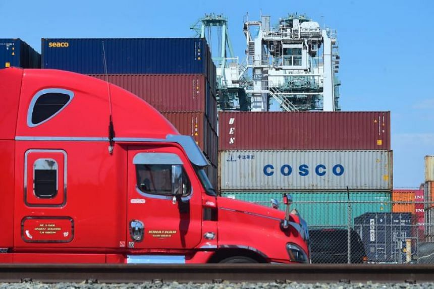 A container delivery truck passes containers stacked at the Port of Long Beach in Long Beach, California, on July 6, 2018.