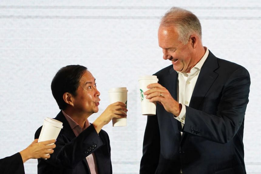 Starbucks CEO Kevin Johnson (right) and Chief Executive Officer of Alibaba Group Holding Ltd. Daniel Zhang toast with cups of Starbucks at a strategic partnership press conference in Shanghai, China, on Aug 2, 2018.