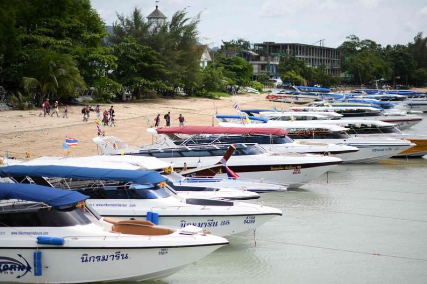 Boats sit lined up near Chalong pier in Phuket on July 6, 2018, as rescue operations continue nearby for missing tourists following a boating accident the day before.