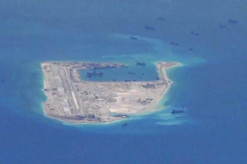 A file screengrab from a video taken by a surveillance aircraft provided by the US Navy on May 21, 2015, shows Chinese dredging vessels purportedly in the waters around Fiery Cross Reef in the disputed Spratly Islands in the South China Sea.