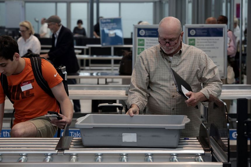 A traveller placing his laptop in a bin for scanning at Terminal 4 of JFK airport in New York City, US, on May 17, 2017.