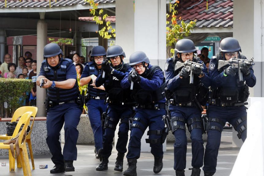 """Home Team officers moving in on a coffee shop being attacked by armed """"terrorists"""" in Teck Ghee on March 18, 2017, as part of an exercise on Emergency Preparedness Day."""