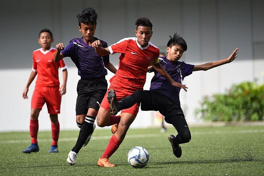 Singapore Sports School captain Amir Syafiz Abdul Rashid (centre, in red) challenged by two Queensway Secondary School players during the Schools National C Division football final at Our Tampines Hub yesterday. Amir scored the winning goal in SSP's
