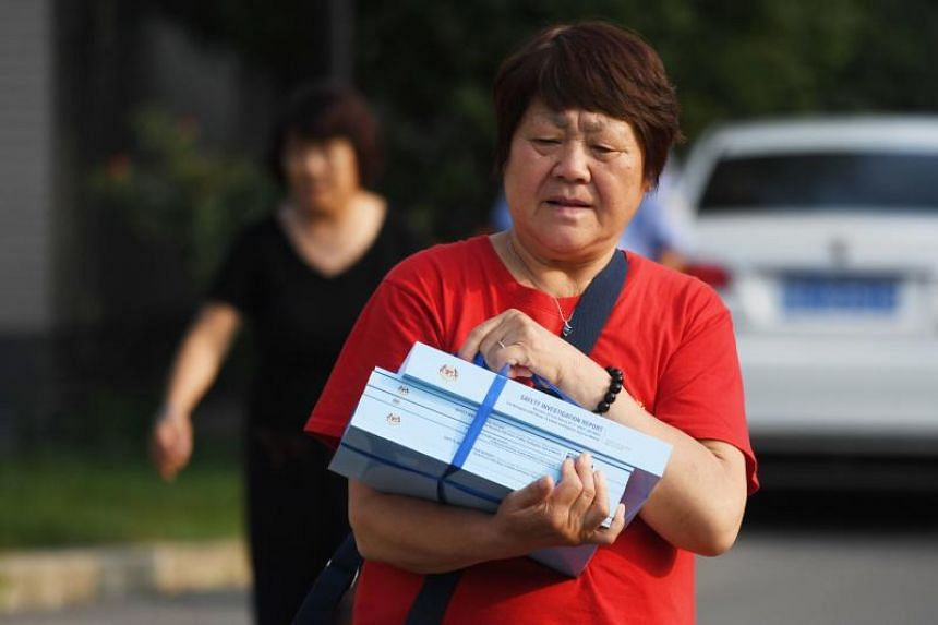 A relative walks out with copies of the official report on the disappearance of Malaysia Airlines MH370, after a meeting with Malaysian officials in Beijing on Aug 3, 2018.