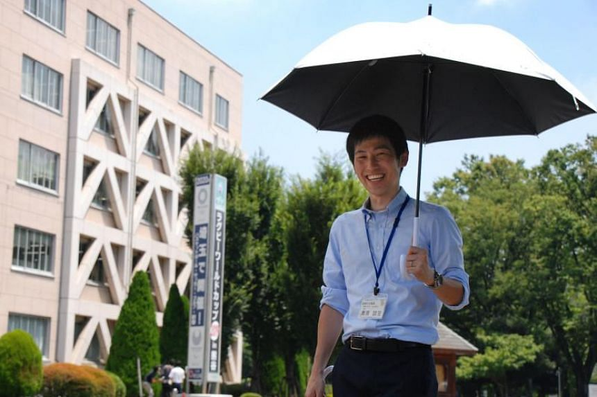 An official of the Saitama prefecture promotes the use of a parasol in Saitama on Aug 1, 2018.