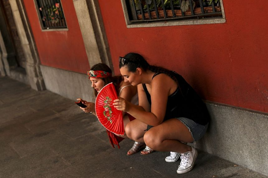 Tourists rest in the shade as temperatures soar throughout the country, in Madrid, Spain, on Aug 2, 2018.