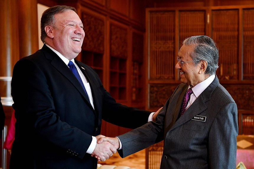 Malaysia's Prime Minister Mahathir Mohamad (right) shakes hands with US Secretary of State Mike Pompeo, who intends to congratulate the former on his coalition's victory.