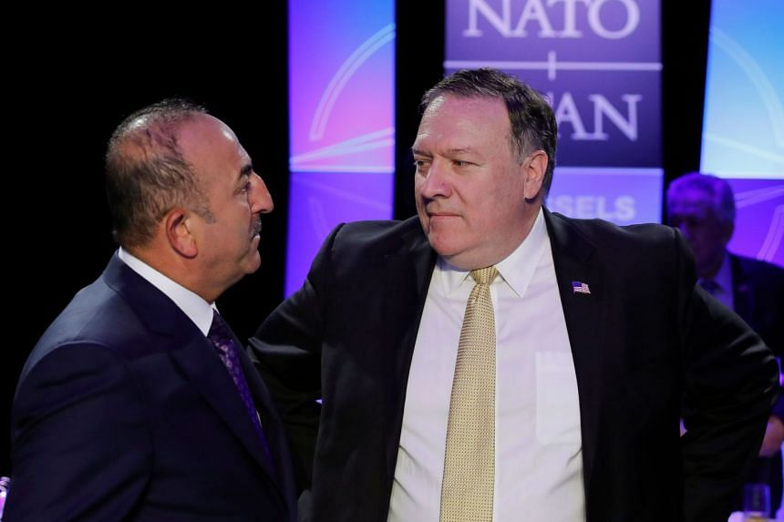 Turkey's Foreign Minister Mevlut Cavusoglu and Acting U.S. Secretary of State Mike Pompeo gesture during a NATO Summit, in central Brussels, on July 11, 2018.