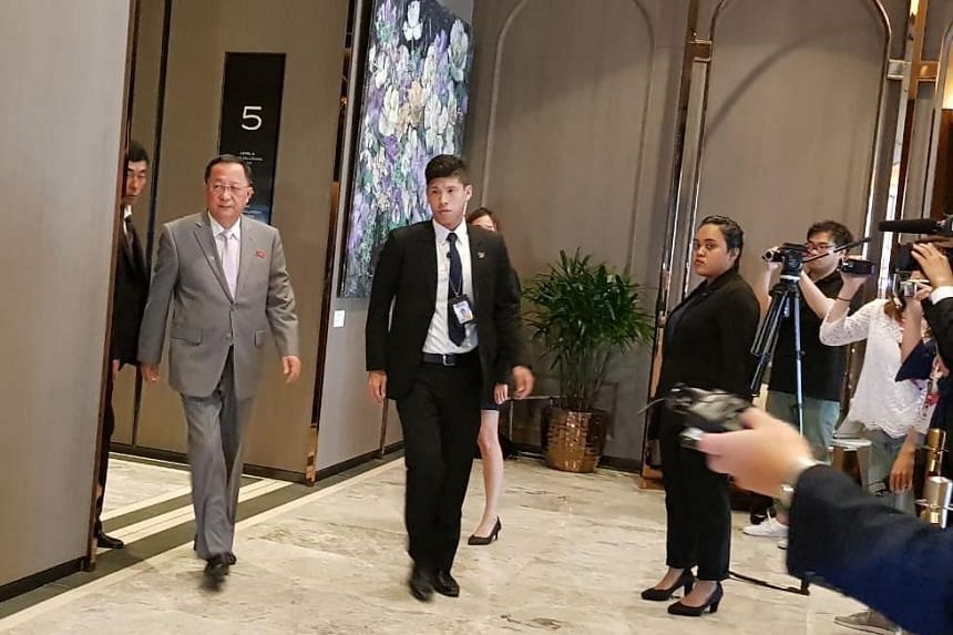 North Korea Foreign Minister Ri Yong Ho (left) leaving the Sofitel Singapore City Centre where he is staying. He did not take any questions from reporters.
