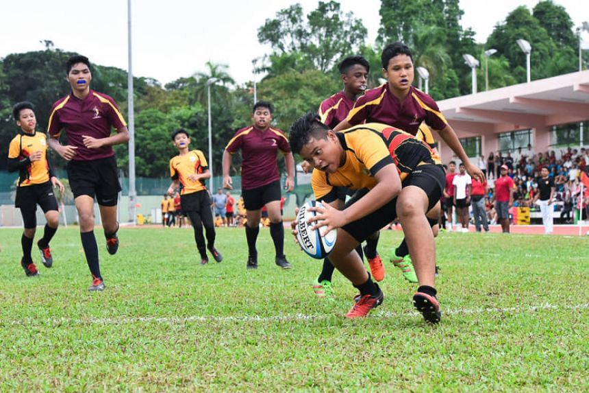 Muhammad Khaireel Aiman Bin Khamsul (front) from Bukit Batok Secondary School scores a point for his team as he touches down in the end zone.