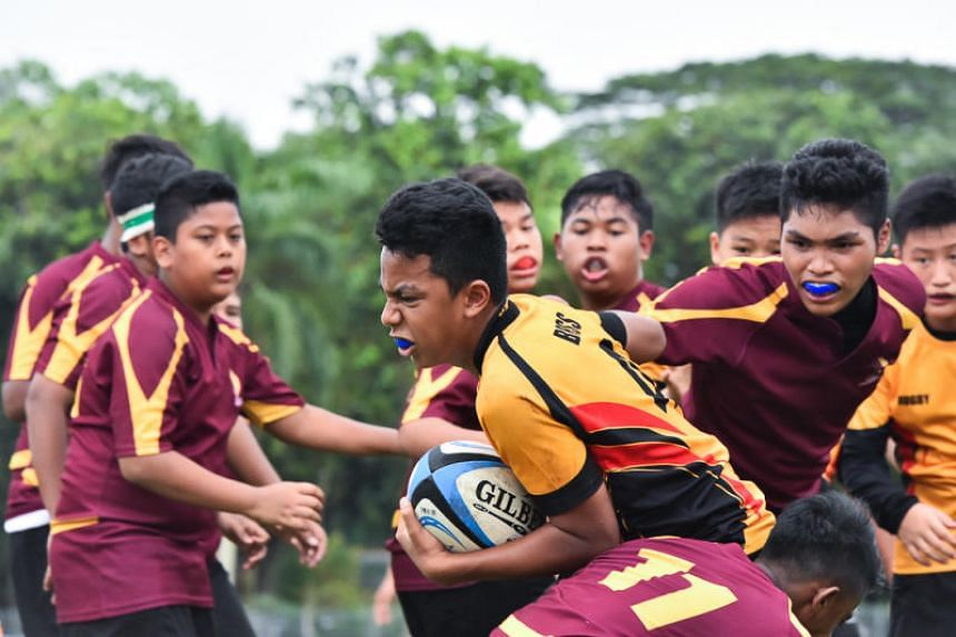 Dani Khairin Bin Mohammad Farouk (front) from Bukit Batok Secondary School attempts to break Damai Secondary School's defence line during the match on Aug 1, 2018.