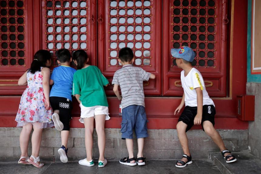 Children look inside through a window at the Forbidden City in central Beijing, China, on July 31, 2018.