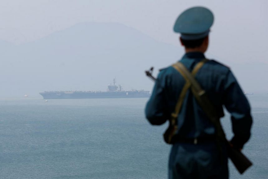 A Vietnamese soldier keeps watch in front of U.S. aircraft carrier USS Carl Vinson after its arrival at a port in Danang, Vietnam, on March 5, 2018.