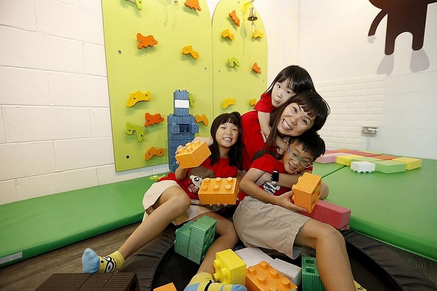 Ms Beverlyn Ong with her three children - four-year-old Charlyn (behind mum); Benjamin, seven; and Ashlyn, eight. Ms Ong has registered them for a series of activities being held at Singapore Sports Hub.