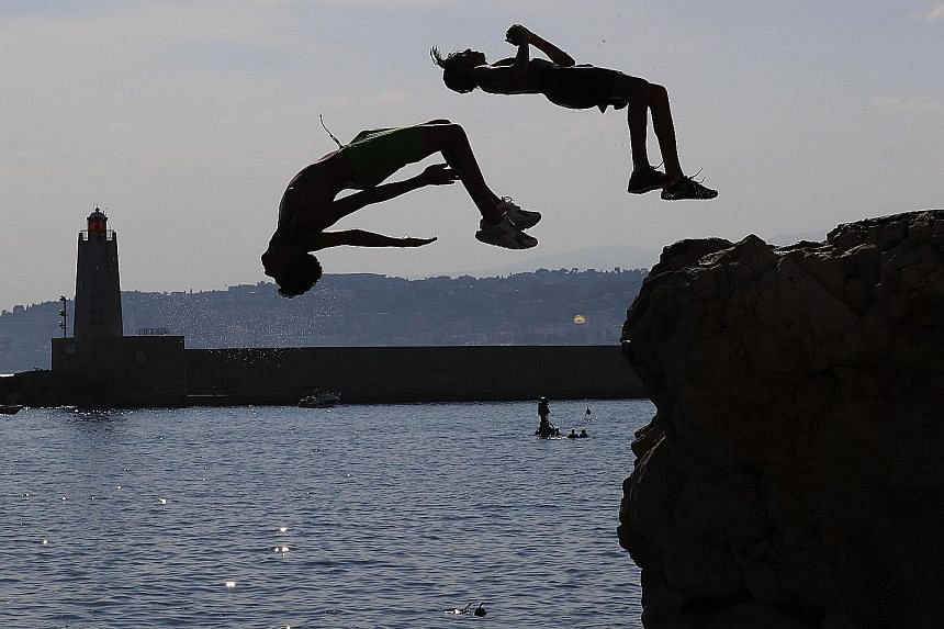 Young men leaping off rocks into the ocean on Thursday in Nice, France. A heatwave warning was in place across much of southern and eastern France on Thursday, and vacationers have been warned to take precautions against extreme temperatures.