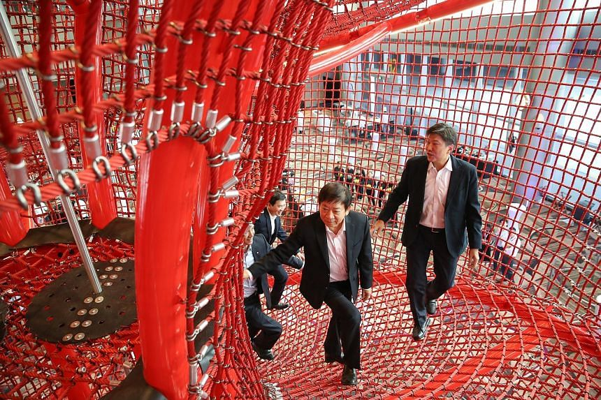 Transport Minister Khaw Boon Wan and Minister in the Prime Minister's Office and labour chief Ng Chee Meng taking a look at the Chandelier, a rope and steel structure at the new playground in Terminal 4.