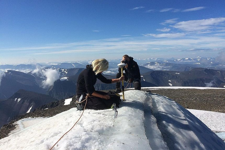 Stockholm University geography professor Gunhild Ninis Rosqvist making measurements on Tuesday atop a glacier on the southern tip of the Kebnekaise mountain in northern Sweden, which is melting due to record hot Arctic temperatures.